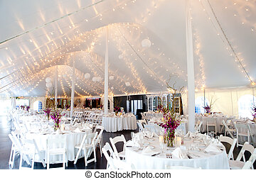 wedding tables set for fine dining inside a tent
