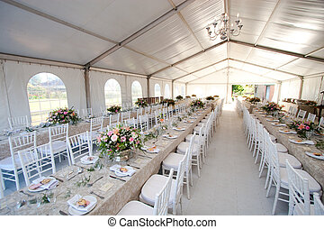The inside of a massive white wedding tent with tables and chairs already in position