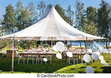 Wedding tent with large balls. Tables sets for wedding or another catered event dinner