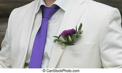 The groom dressed in a white suit with purple tie
