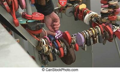 Wedding tradition. Bride hangs padlock on tube - Wedding...