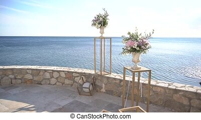 wedding venue decorations with stands, glass pendants and vases with flowers. High quality FullHD footage