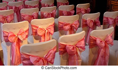 Wedding venue seating - White decorated chairs with pink...