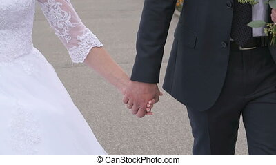 Bride and groom holding hands during walking - Wedding...