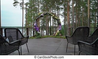 Wedding. Wedding ceremony. Arch, decorated with violet and yellow flowers standing in the woods, in the wedding ceremony area