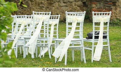 Wedding white chairs decorated with a silk ribbons