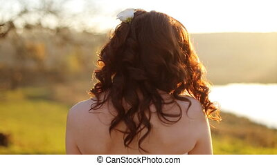 Wedding. Young beautiful bride with hairstyle and makeup posing in white dress and veil. Soft sunset light  portrait. Girl looking in camera shot in slow motion  close up
