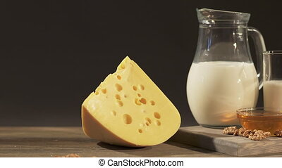 Wedge of Swiss cheese with jug of milk on old wooden table -...