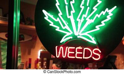 Weeds front store night - Illuminated sign marijuana leaf...