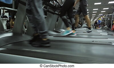 weekdays gym, several people on the treadmill every move at different speeds, some tracks are in a row, a mirror and a large amount of light in the frame.
