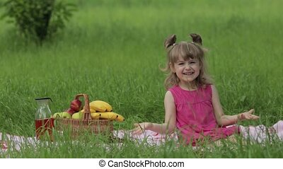 Weekend at picnic. Lovely caucasian child girl on green grass meadow sit on blanket waving her hands