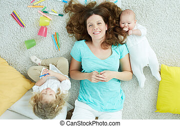 The above-view portrait of a charming mother relaxing with her kids on the weekend