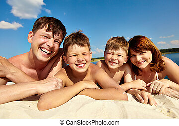 Weekend - Photo of happy family lying on sand on summer ...