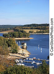 Small yachts leave their moorings on Lac de Vassiviere, Limousin, France to participate in an afternoon of racing.