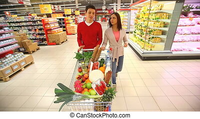 Weekend shopping - Young couple pushing shopping cart full...