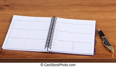 Weekly Planner - Opened weekly planner on a desk with a pen