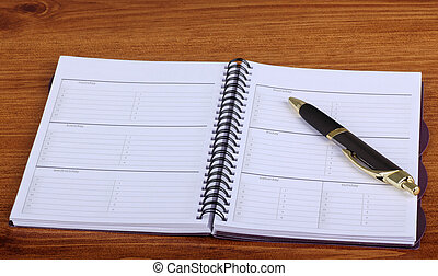Weekly Planner - Opened weekly planner with a pen on a desk ...