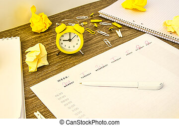 Weekly planner with alarm clock and office supplies. ...