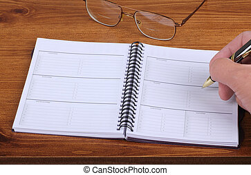 Weekly Planner - Writing in an opened weekly planner on a ...