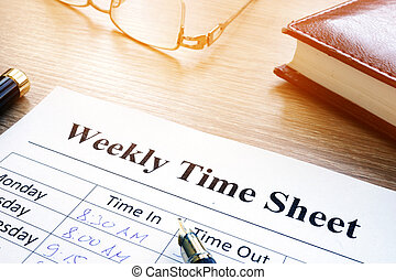 Weekly time sheet and pen on an office desk.