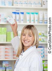 weibliche , apotheker, nehmen medizin, kasten, von, regal