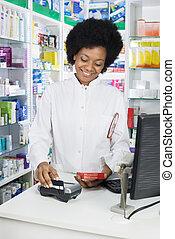 weibliche , apotheker, swiping, kreditkarte, während, besitz, produkt