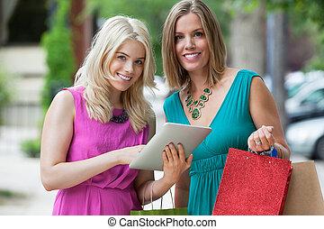 weibliche , friends, mit, einkaufstüten, gebrauchend, digital tablette