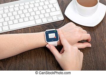 weibliche hand, mit, weißes, smartwatch, mit, e-mail, auf, der, schirm, aus, a, holztisch, in, ein, buero