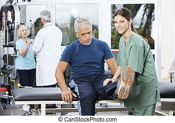 weibliche , krankenschwester, assistieren, älterer mann, in, bein, übung