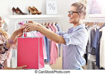 weibliche , kunde, annahme, einkaufstüten, in, kleiderladen