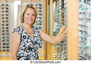 weibliche , kunde, auswählen, brille, in, optiker, kaufmannsladen