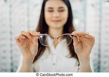 weibliche , kunde, hält, brille, in, hand, optisch, kaufmannsladen