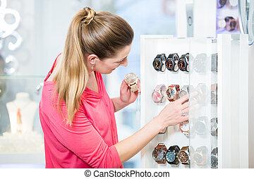 weibliche , kunde, in, kaufmannsladen, sehen, armbanduhren