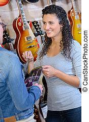 weibliche , kunde, sehen, neu , gitarre, in, kaufmannsladen, und, lächeln