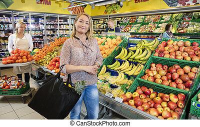 weibliche , kunde, stehende , per, frische früchte, in, lebensmittelgeschäft, laden