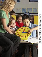 weiblicher lehrer, in, grundschule, unterricht, kinder, erzählen, zeit, in, klassenzimmer