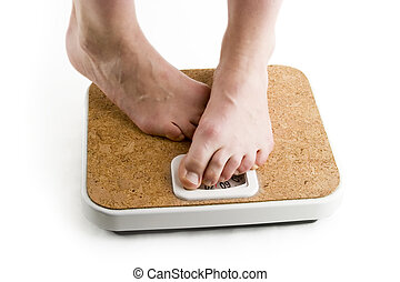 Weighing In - A pair of female feet standing on a bathroom...