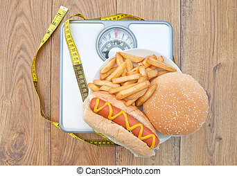 Fattening foods on weighing scales with a tape measure, including burger chips and hot dog