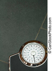 Weighing scales on a slate floor with copyspace