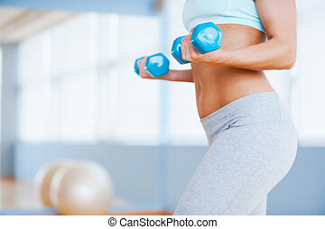 Weight exercise. Cropped image of beautiful young woman in sports clothing exercising with dumbbells while standing in health club