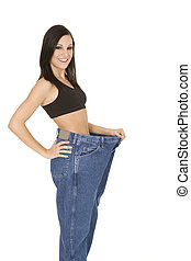 Weight Issues - Caucasian woman hold old jeans to show...