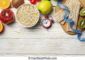 Weight loss accessories on wooden background, top view