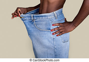 Weight loss - African American woman with huge trousers,...