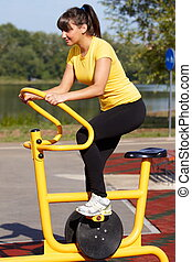 Girl exercising on bicycle machine in a park
