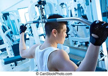 weight training - asian man using lat pulldown machine in...