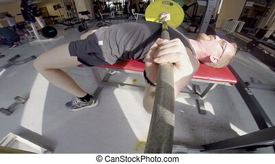 Male trainer in sport club. He makes the bench press. The camera is attached to the barbell