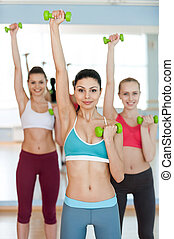 Weight training. Three beautiful young women in sports clothing exercising with dumbbells and smiling at camera