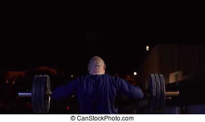 Weightlifter lifts the bar above his head. Strength training with a huge weight. strong crossfit athlete in the middle a heavy snatch lift in a cross-fit box gym