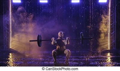 Weightlifter lifts the bar above his head. Strength training with a huge weight. Raindrops fall on the wet muscular body. Black background with blue light. Slow motion.