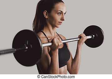 Weights lifting - Shot of a beautiful young woman in a ...
